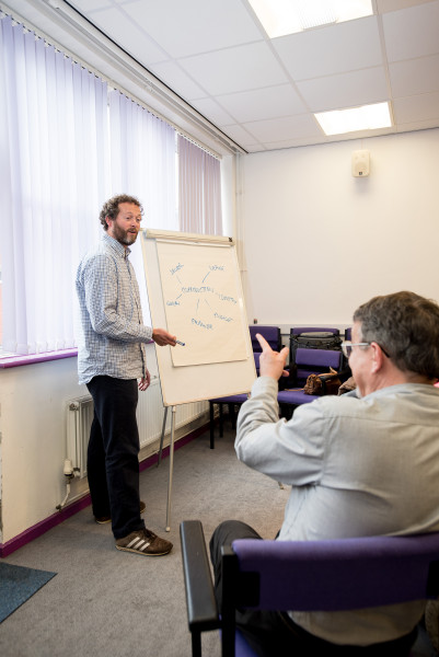 A staff member delivering a training session and pointing to notes on a flipchart