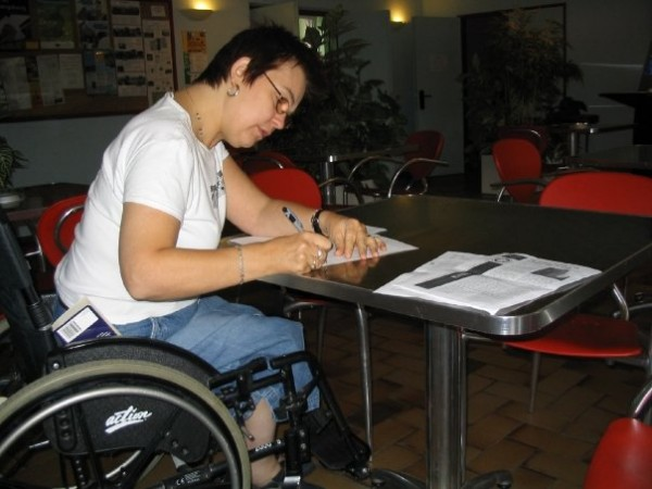 Disabled woman writing at a desk