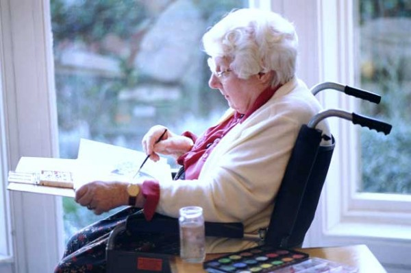 Photo of a Disabled Woman working on a painting